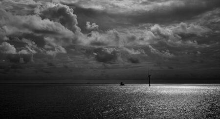 Molino de viento en el mar y el cielo con nubes al amanecer, litoral de Gran Canaria, Islas Canarias, España, modo blanco y negro