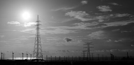 Industrial landscape at sunrise with high voltage towers and wind turbines, monochrome mode