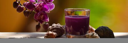 Photographic composition with orchid flowers, candle in glass and small seashells