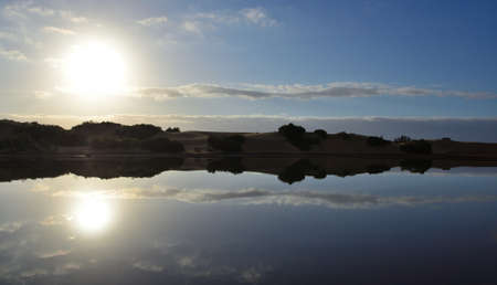 Awesome sunrise with reflections in the water, Charca de Maspalomas, Gran Canaria, Canary Islands, Spain Standard-Bild