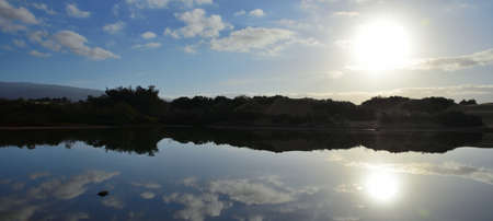 Sunrise from the lagoon with reflections in the water, Charca de Maspalomas, south of Gran Canaria, Spain