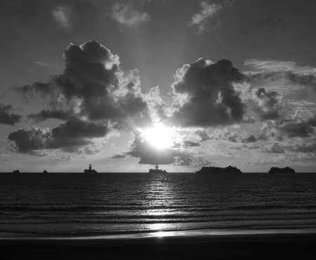 Sunrise from the beach with calm sea, ships and sky with low clouds, monochrome mode