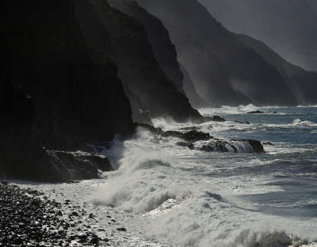 Rough sea and silhouettes of high cliffs, coast of Agaete, northwest of Gran Canaria, Canary Islands, Spain
