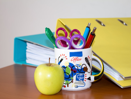 pen holder: Photo of files, apple and pens in a pen holder in an office Stock Photo