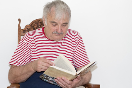 Photo of an old man enjoying reading a book on a Sunday afternoon