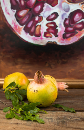 scarred: Image of whole scarred unripe pomegranates with a blurred painting background on rustic table