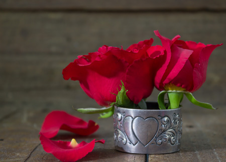 narrow depth of field: Narrow depth of field shot of red roses on rustic wood inside antique silver heart serviette holder