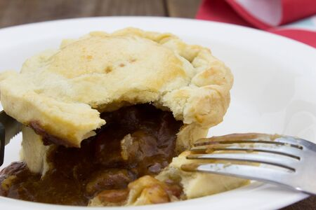 short crust pastry: Steak pie and gravy close up on wood