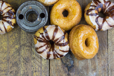 wood cutter: Close up top view of various doughnuts and vintage cutter isolated on rustic wood background Stock Photo