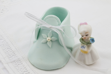 booty: Blue fondant baby booty next to little lady porcelain figurine isolated on white lace