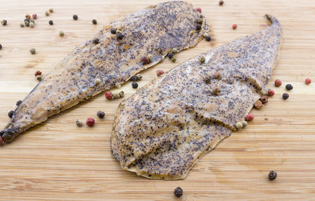 peppered: Two peppered, mustard encrusted smoked mackerel on wood cutting board