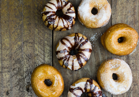 dribbled: Top view photo of six doughnuts on rustic wood table Stock Photo