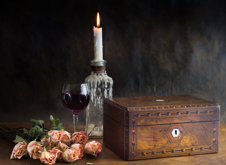 Still life background with roses, antique walnut parquet jewelry box, candle and wine glass