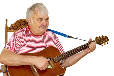 Old grey haired caucasian man playing an acoustic guitar