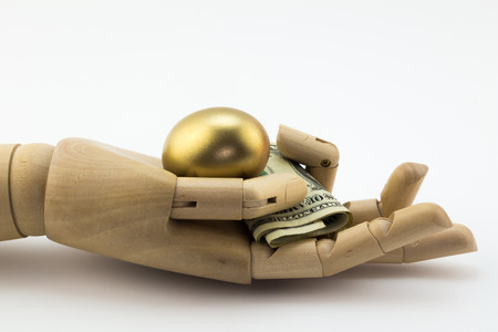 retiring: Golden nest egg in palm of wooden hand with dollar notes isolated on white