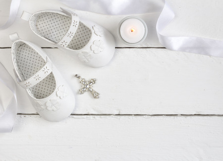 Obenliegendes Foto von Paaren von weißen Babyschuhen, von Kerze und von christlichem Kreuzanhänger auf weißer hölzerner Tabelle