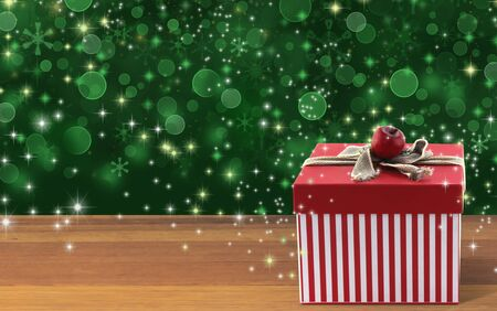 Red striped gift box on wood table with sparkle green background