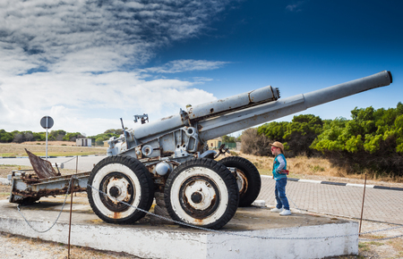 robben island: Little boy looking at the Second World War coastal defence howitzer on Robben Island Stock Photo