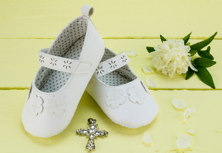 Baptism background of white baby booties and crystal pendant cross on yellow painted wood table