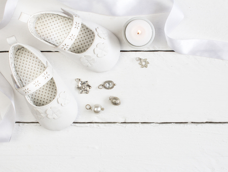 Overhead photo of pair of white baby booties, candle, ribbon and charms on white painted table