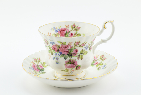 tarde de cafe: Empty antique cup and saucer with rose decoration isolated on white - English tea Foto de archivo