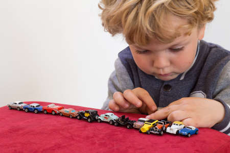 Little blonde boy playing with vintage toy cars on red velvet pouf chair