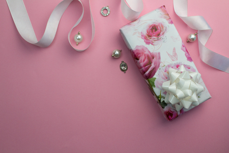 Pink background with wrapped gift, white satin ribbon and pearl and crystal charms for Mothersday