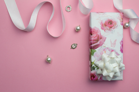 Mothers day pink background with wrapped gift, white satin ribbon and pearl and crystal charms