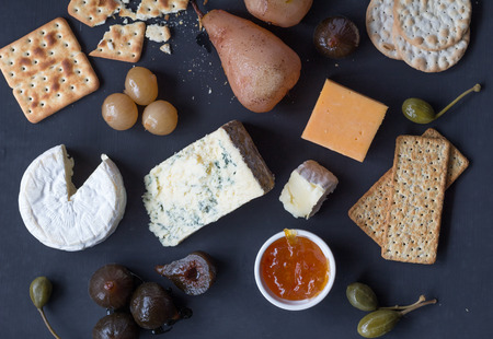 Cheese and crackers served with caper berries, figs, marmalade and pickled onions on black board. Top view photograph