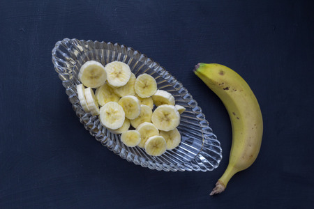 Banana slices in glass bowl with whole unpeeled banana on black background - Top view photograph