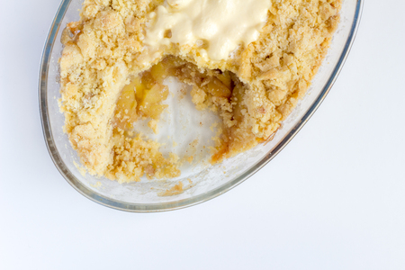 Cooked cinnamon apple crumble pie in glass oval dish on white background - Top view Stock Photo