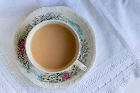 Cup of tea close up on lace cloth in vintage cup and saucer - Top view background Reklamní fotografie