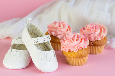 Baptism or birthday girl invitation with pink cup cakes and white shoes on pink background