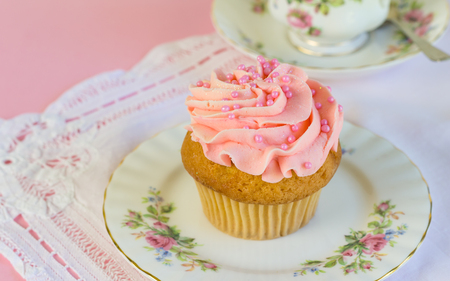 Pink glitter and pearl frosted cup cake on plate with teacup in background - space for text Stock Photo