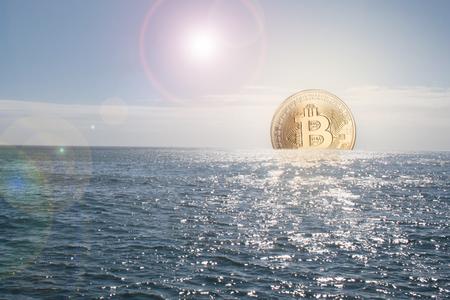 Bitcoin currency rising / sinking concept in ocean and golden bitcoin as the sun Reklamní fotografie