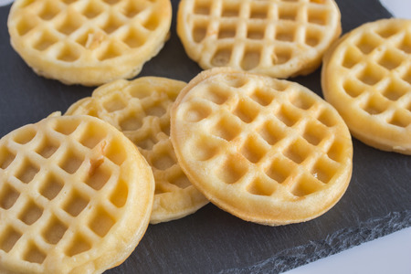 Round small waffles on black slate board with selective focus