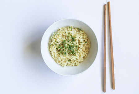 Noodles in bowl with chopsticks isolated on white