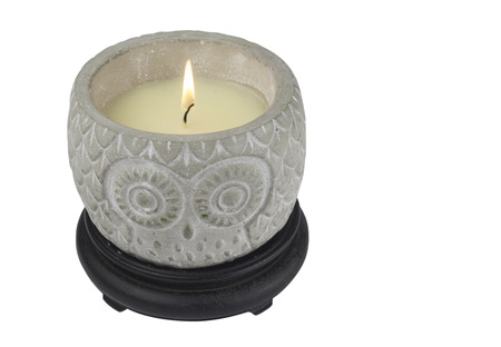 Candle in decorative owl motive decorated candle holder isolated on white background