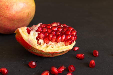Rustic piece of pomegranate fruit on black table close up with selective focus on slice of fruit Foto de archivo