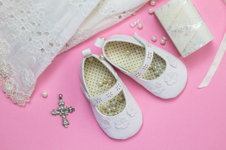 Baptism dress, shoes, crystal cross pendant, pearls and little mother of pearl box isolated on pink background - top view photo of baby girl's christening objects