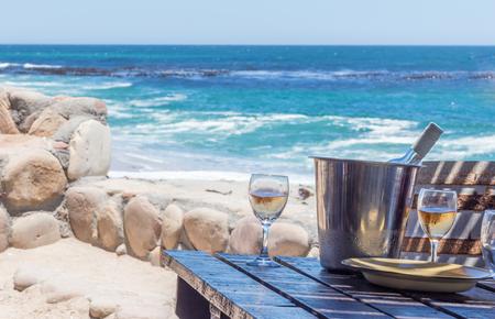 Wine glasses at a rustic beach restaurant table facing the Atlantic Ocean - Image