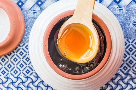 Raw African honey in a ceramic honey pot with wooden spoon on ethnic blue cloth Standard-Bild - 121049606