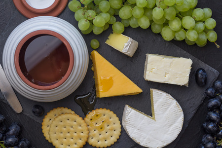Cheese board with cheddar, camembert, grapes, crackers and honey close up - top view Standard-Bild - 121049609