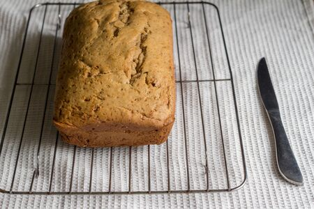 Banana bread loaf on cake grid on white dishtowel background