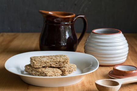 Cereal bars in bowl, with milk and honey jar in background Standard-Bild - 128904277