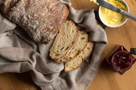 Sourdough bread and slices with butter and knife on kitchen cloth - Overhead image