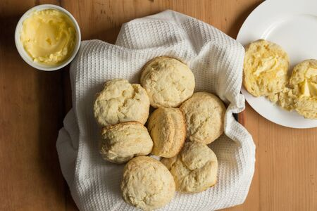 Scones in a dish towel with sliced scones, buttered in a plate - Overhead photo