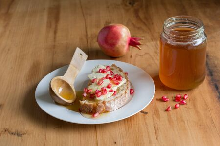 Bread, cheese, honey and pomegranate on rustic wooden table - Food still life Imagens - 128900231