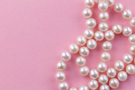 Pearl background with nacreous pearl necklace on pink background - close up macro photo