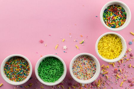 Sprinkles on pink background - Assorted colourful cake topping sprinkles in little white bowls on pink - top view